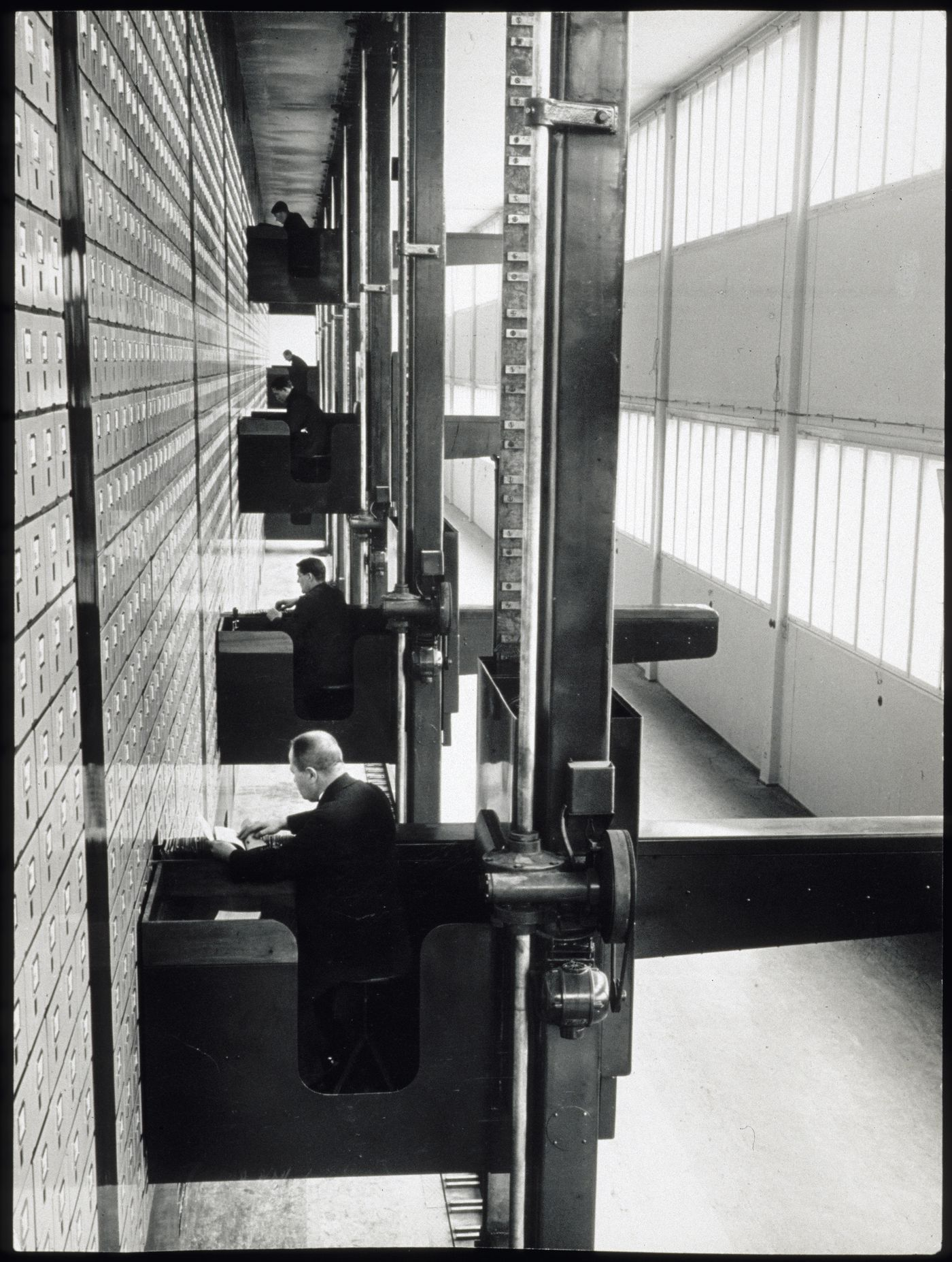 Interior view of the Central Social Insurance Institution showing men working in mobile work stations used to access the card catalog drawers, Prague, Czechoslovakia (now Czech Republic)