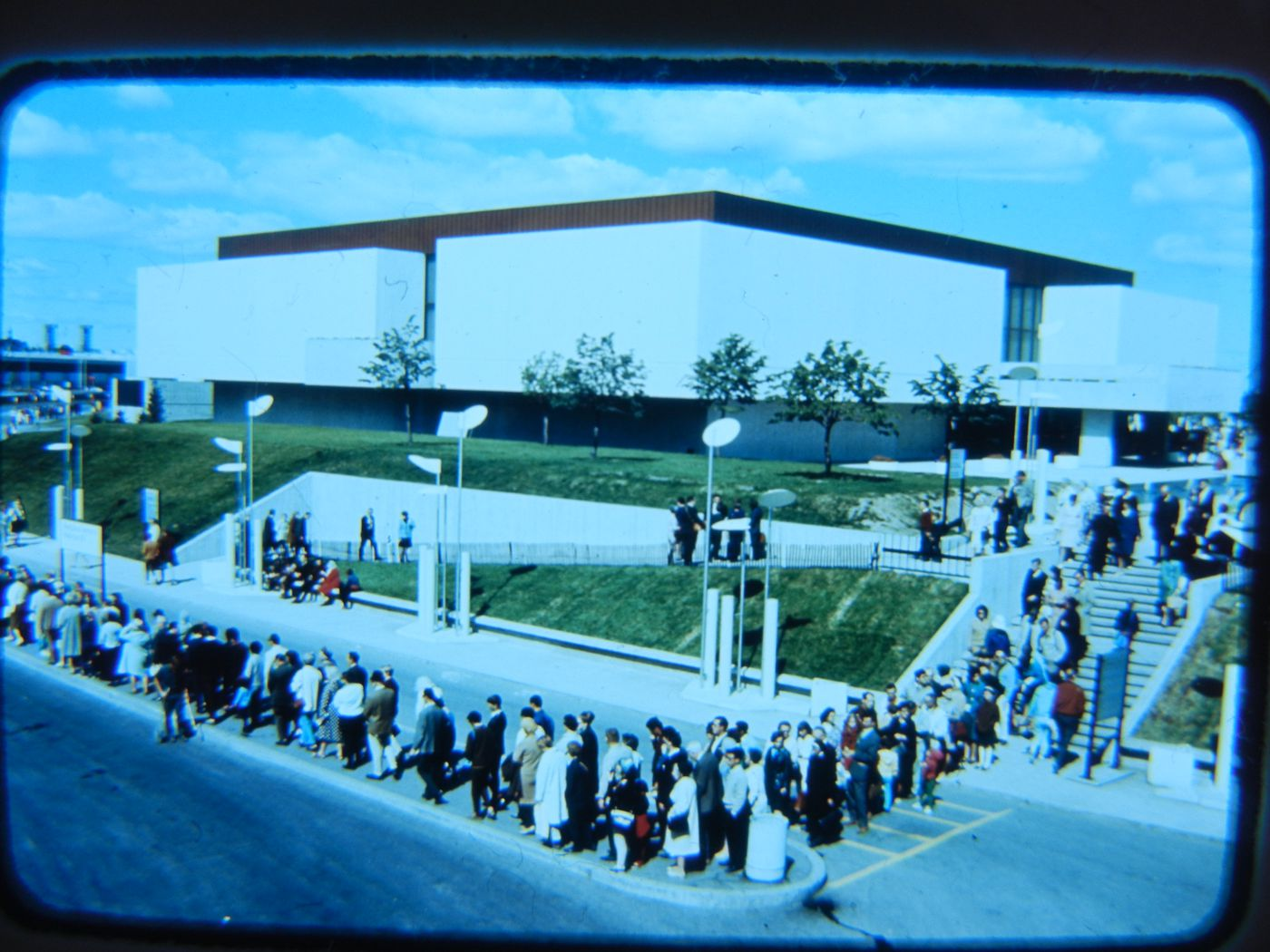 View of the Man the Creator Pavilion with visitors standing in line at a trailer train stop in foreground, Expo 67, Montréal, Québec