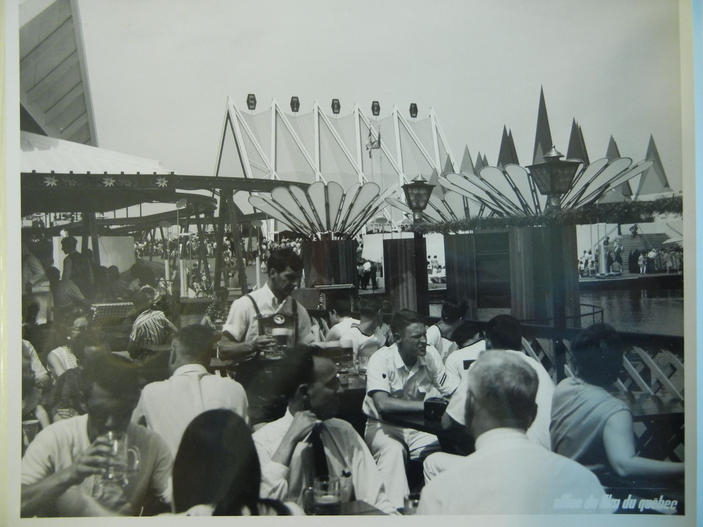 View of seated visitors drinking beer at the Expo-Services C with the Steel Pavilion in background, Expo 67, Montréal, Québec